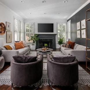 Ispirazione per un soggiorno chic di medie dimensioni e aperto con pareti nere, parquet scuro, camino classico, cornice del camino in pietra, TV a parete e pavimento marrone