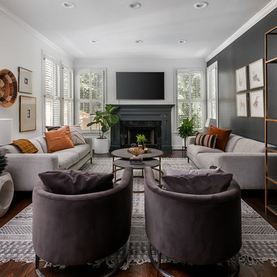 Example of a mid-sized transitional open concept dark wood floor and brown floor living room design in Atlanta with black walls, a standard fireplace, a stone fireplace and a wall-mounted tv