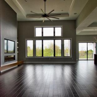 Diseño de salón abierto, moderno, grande, con paredes grises, suelo de madera oscura, chimenea lineal, marco de chimenea de yeso, televisor colgado en la pared y suelo marrón