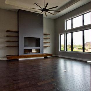 Modelo de salón abierto, moderno, grande, con paredes grises, suelo de madera oscura, chimenea lineal, marco de chimenea de yeso, televisor colgado en la pared y suelo marrón