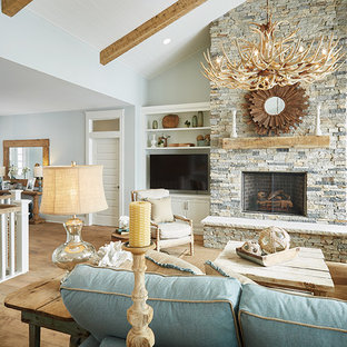 Living room - large beach style open concept medium tone wood floor living room idea in Grand Rapids with a bar, blue walls, a standard fireplace, a stone fireplace and a media wall