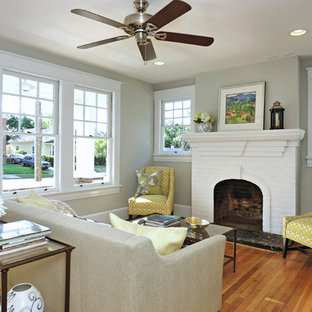 Living room - mid-sized traditional living room idea in Raleigh with gray walls, a standard fireplace and a brick fireplace