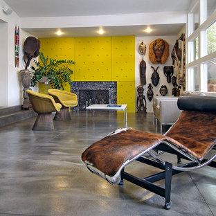 Cette image montre un salon bohème avec béton au sol, une cheminée standard et un manteau de cheminée en carrelage.