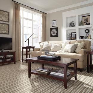 Foto di un soggiorno stile americano di medie dimensioni e chiuso con pareti beige, parquet chiaro, nessun camino e TV autoportante