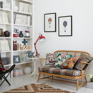 Photo of a scandinavian living room in London with a reading nook, white walls and light hardwood flooring.