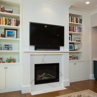 Immagine di un soggiorno chic aperto con angolo bar, pareti bianche, pavimento in legno massello medio, camino classico, cornice del camino in pietra e TV a parete