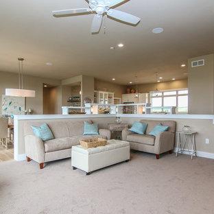 他の地域の広いビーチスタイルのおしゃれなLDK (ベージュの壁、カーペット敷き、標準型暖炉、石材の暖炉まわり、据え置き型テレビ、ベージュの床) の写真