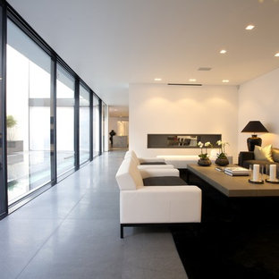 Inspiration for a modern living room in London with white walls, a two-sided fireplace and grey floors.