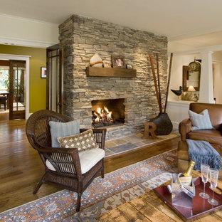 Esempio di un grande soggiorno stile americano aperto con cornice del camino in pietra, pareti beige, pavimento in legno massello medio e camino classico