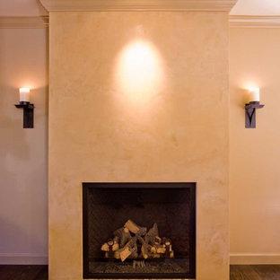 Ispirazione per un grande soggiorno boho chic aperto con sala formale, pareti beige, parquet scuro, camino classico e cornice del camino in intonaco