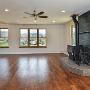 Inspiration for a large farmhouse formal and open concept medium tone wood floor and brown floor living room remodel in Other with beige walls, a wood stove, a stone fireplace and no tv