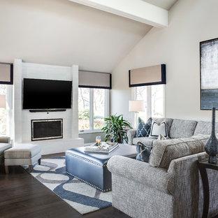 Foto de salón con barra de bar abierto, clásico renovado, grande, con paredes grises, suelo de madera oscura, chimenea tradicional, marco de chimenea de baldosas y/o azulejos y televisor colgado en la pared