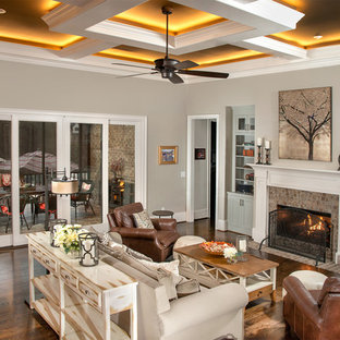 Example of a large classic formal and open concept dark wood floor living room design in Other with beige walls, a standard fireplace and a media wall