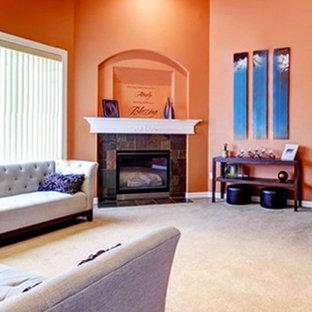 Diseño de salón tradicional, grande, con parades naranjas, moqueta, chimenea tradicional, marco de chimenea de piedra y televisor colgado en la pared