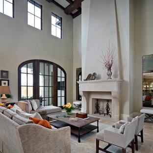 ヒューストンの広い地中海スタイルのおしゃれなLDK (フォーマル、グレーの壁、トラバーチンの床、標準型暖炉、石材の暖炉まわり、テレビなし) の写真