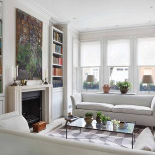Esempio di un soggiorno design di medie dimensioni e chiuso con libreria, pareti bianche, camino classico, cornice del camino in pietra, nessuna TV, pavimento beige e pavimento in vinile