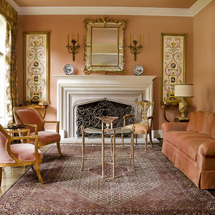 Example of a mid-sized classic formal and enclosed medium tone wood floor living room design in Dallas with orange walls, a standard fireplace, a wood fireplace surround and no tv