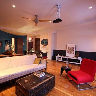 Idee per un grande soggiorno moderno stile loft con pareti beige, pavimento in legno massello medio e TV nascosta