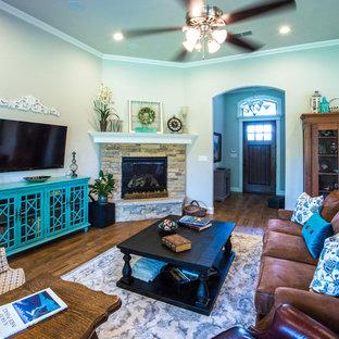 ダラスの大きいラスティックスタイルのおしゃれな独立型リビング (ベージュの壁、無垢フローリング、標準型暖炉、石材の暖炉まわり、壁掛け型テレビ、茶色い床) の写真