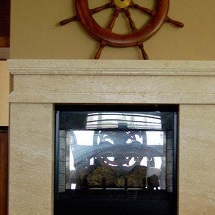 タンパの広いトロピカルスタイルのおしゃれなLDK (黄色い壁、無垢フローリング、両方向型暖炉、石材の暖炉まわり、テレビなし、茶色い床) の写真