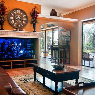 Foto de salón abierto, de estilo americano, grande, sin chimenea, con parades naranjas, suelo de baldosas de cerámica y pared multimedia