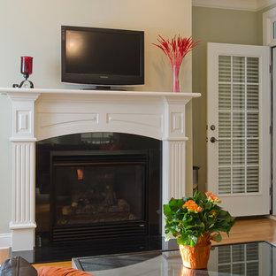 Foto di un piccolo soggiorno chic chiuso con sala formale, pareti marroni, pavimento in legno massello medio, camino classico, cornice del camino in legno e TV autoportante