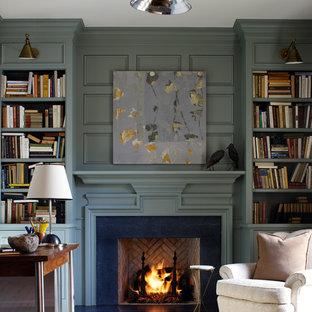 Foto di un soggiorno chic con libreria, camino classico, cornice del camino in pietra e pareti verdi