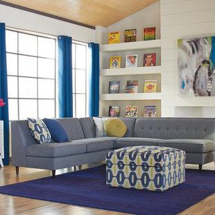 Esempio di un ampio soggiorno minimalista aperto con pareti bianche, pavimento in legno massello medio, camino classico e cornice del camino in intonaco