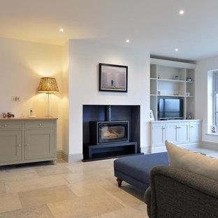 Ejemplo de salón abierto, tradicional renovado, de tamaño medio, con suelo de piedra caliza, estufa de leña, marco de chimenea de yeso y televisor independiente