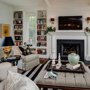 Ejemplo de salón clásico con paredes blancas, chimenea tradicional, marco de chimenea de piedra y televisor colgado en la pared