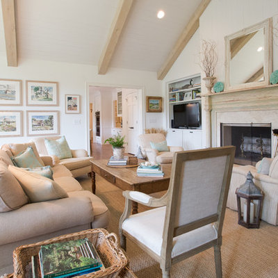 Example of a farmhouse medium tone wood floor living room design in Atlanta with white walls and a standard fireplace