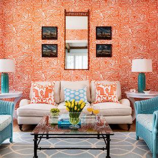 Réalisation d'un grand salon ethnique fermé avec une salle de réception, un mur orange, un sol en bois clair, aucune cheminée, aucun téléviseur et un sol beige.