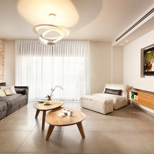 Trendy concrete floor living room photo in Other with a wall-mounted tv