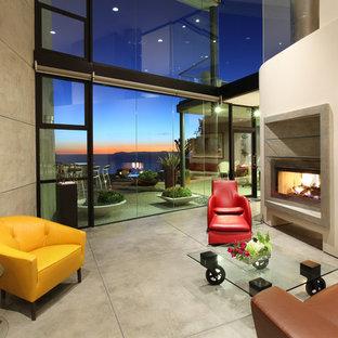 オレンジカウンティのトロピカルスタイルのおしゃれなリビング (コンクリートの暖炉まわり、コンクリートの床) の写真