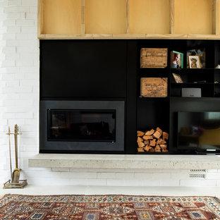 Foto di un soggiorno moderno di medie dimensioni e chiuso con pareti bianche, pavimento in cemento, stufa a legna, cornice del camino in metallo, TV a parete e pavimento grigio