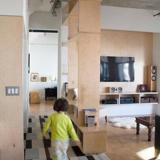 Immagine di un soggiorno moderno di medie dimensioni e stile loft con libreria, pareti bianche, pavimento in sughero, nessun camino e parete attrezzata