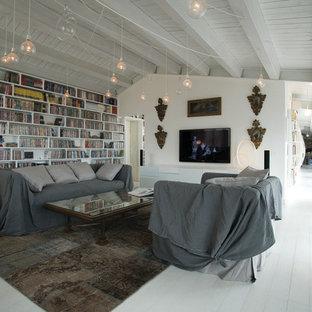 Ejemplo de biblioteca en casa contemporánea, grande, con paredes blancas, suelo de madera pintada y televisor colgado en la pared
