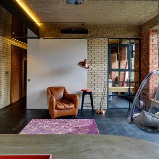 Design ideas for an industrial living room in London with beige walls, dark hardwood flooring and black floors.