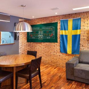 Foto di un grande soggiorno minimalista aperto con angolo bar, pareti grigie e pavimento in legno massello medio