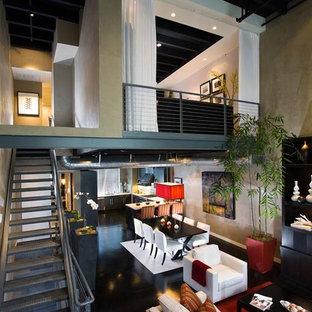 Idee per un ampio soggiorno minimalista stile loft con pavimento nero, pareti beige e pavimento in compensato
