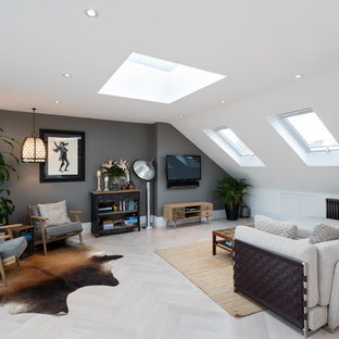 Photo of a medium sized contemporary open plan living room in London with multi-coloured walls, a wall mounted tv, grey floors and light hardwood flooring.