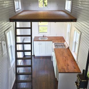 Diseño de salón abierto, tradicional, pequeño, sin televisor, con paredes blancas, suelo de madera oscura, estufa de leña y marco de chimenea de metal