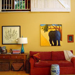 Ejemplo de biblioteca en casa tipo loft, campestre, grande, sin televisor, con paredes amarillas, estufa de leña, marco de chimenea de baldosas y/o azulejos y suelo de madera clara