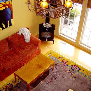 シアトルの大きいおしゃれなリビングロフト (黄色い壁、薪ストーブ、木材の暖炉まわり、淡色無垢フローリング) の写真