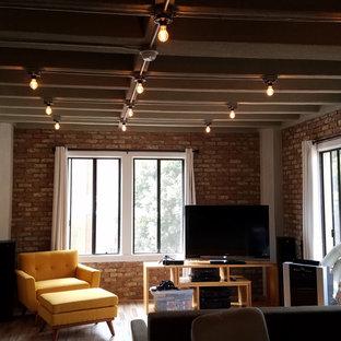 Foto de salón para visitas tipo loft, bohemio, de tamaño medio, con paredes rojas, suelo de madera clara y televisor independiente