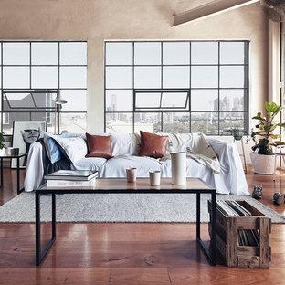 Неиссякаемый источник вдохновения для домашнего уюта: большая открытая гостиная комната в стиле лофт с паркетным полом среднего тона