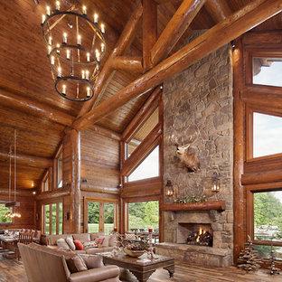 Rustik inredning av ett mycket stort allrum med öppen planlösning, med bruna väggar, mellanmörkt trägolv, en standard öppen spis, en spiselkrans i sten, en väggmonterad TV och flerfärgat golv