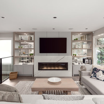 Example of a large trendy open concept brown floor and dark wood floor living room design in Vancouver with gray walls, a ribbon fireplace, a wall-mounted tv and a tile fireplace