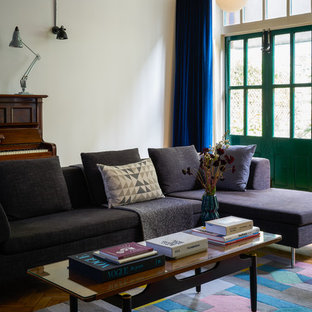 This is an example of an eclectic living room in London with white walls and brown floors.