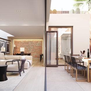 Modelo de salón abierto y ladrillo, minimalista, grande, ladrillo, sin chimenea, con paredes beige, suelo de madera clara, televisor colgado en la pared, suelo beige y ladrillo